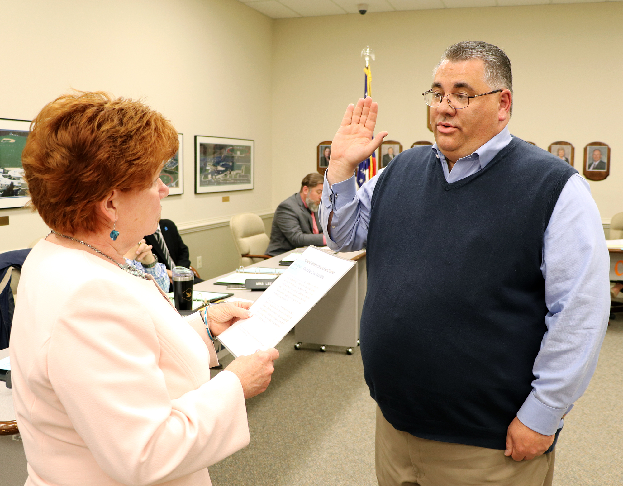 Business Administrator Connie Stewart swearing in new board member Marc Jones